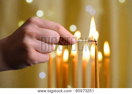 Hand lighting candle