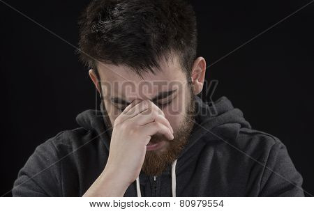 Worried Goatee Young Man with Hand on Face
