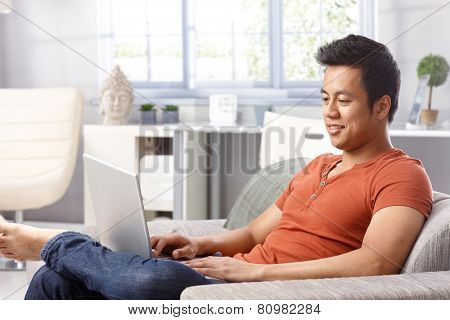 Young man using laptop computer at home, sitting on sofa.
