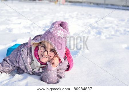 Little girl with glasses playing in the snow