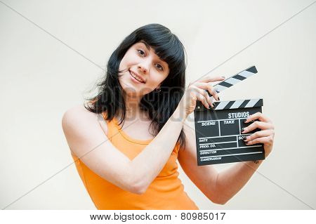 Smiling Brunette Girl Showing Clapper On White Background