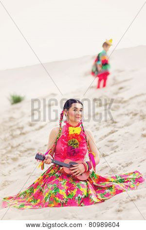 girl dressed in a Mexican outfit and playing little guitar
