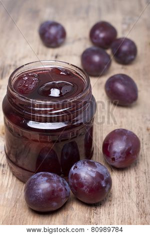 Plum Jam In A Glass Jar And Plums On The Table.