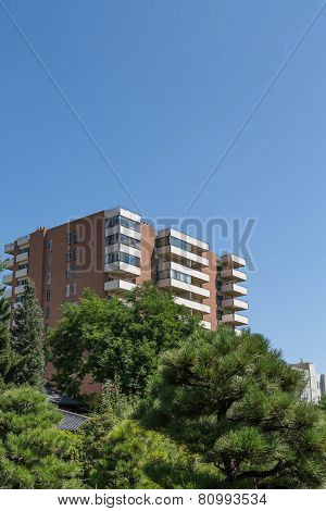 Brown And White Condo Tower In Green Trees