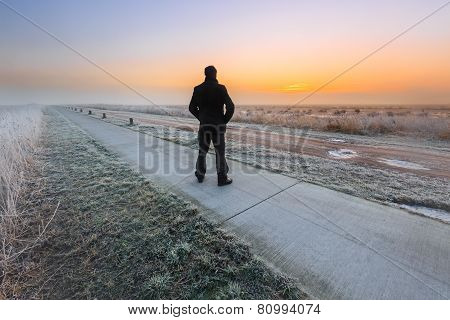 Man Watching The Sunrise On A Cold Winter Day