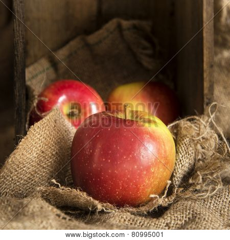 Red Apples In Rustic Kitchen Setting With Old Wooden Box And Hessian Sack