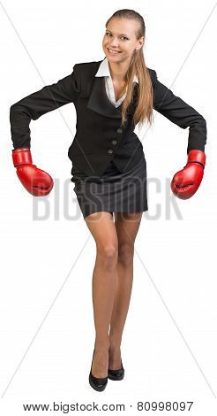 Businesswoman wearing boxing gloves bending forward