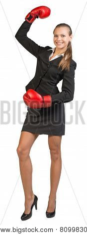 Businesswoman wearing boxing gloves standing with one hand raised, looking at camera, smiling