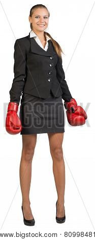 Businesswoman wearing boxing gloves, looking at camera, smiling