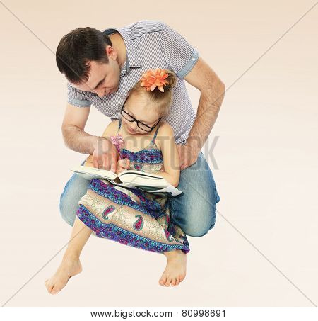 Dad and daughter reading a book.