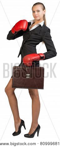Businesswoman wearing boxing gloves holding briefcase