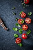 stock photo of slating  - Halved cherry tomatoes and basil leaves on black slate - JPG
