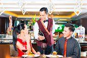 image of waiter  - Waiter serving wine in restaurant - JPG