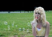 foto of teenage girl  - Young white Caucasian teenage girl laying in grass blowing bubbles - JPG