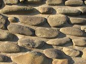 stock photo of elliptical  - solid wall made of many elliptic stones - JPG