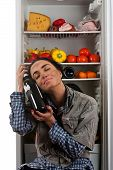 picture of girl next door  - dirty woman sitting next to fridge and hugging a bottle of wine - JPG