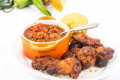 stock photo of jalapeno peppers  - Serving of spicy wings in Honey BBQ Sauce on plate with bowl of homemade chili and Jalapeno cornbread - JPG