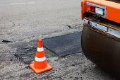 foto of paved road  - Road roller and traffic cone on the road construction - JPG