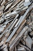 stock photo of slating  - Pile of the old and damaged wavy roofing slates - JPG