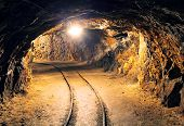 stock photo of tunnel  - Mine gold underground tunnel railroad with light - JPG