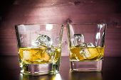 foto of whiskey  - drink series glasses of whiskey with ice on old wood table pub atmosphere - JPG