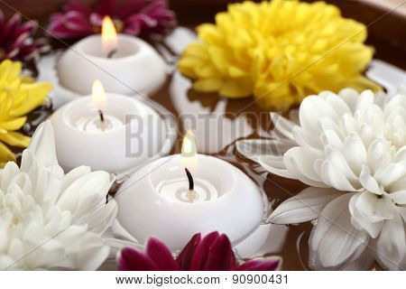 Bowl of spa water with flowers and candles, closeup
