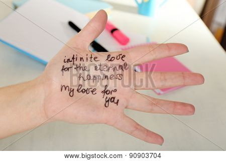Female hand with written message on work place background
