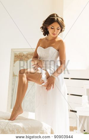 Young Bride Putting Garter On Her Leg