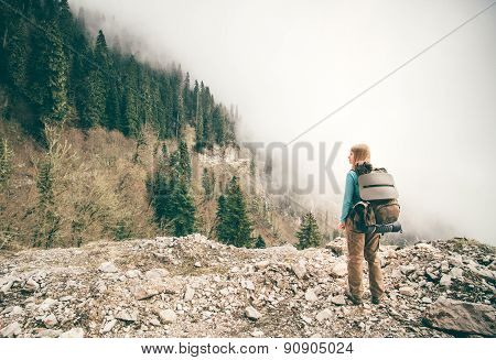 Young Woman with backpack relaxing outdoor with foggy forest on background