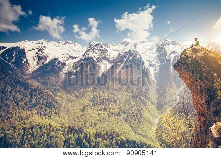 Young Man relaxing on mountain cliff outdoor with mountains on background Lifestyle Travel concept
