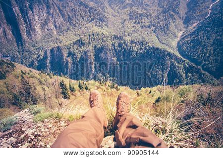 Feet Man Traveler relaxing on cliff mountains outdoor with aerial view on background