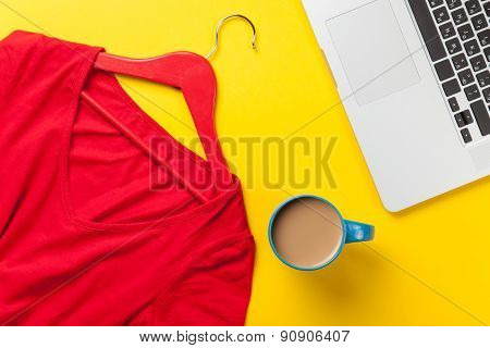 Cup And Laptop Computer Near Red Dress