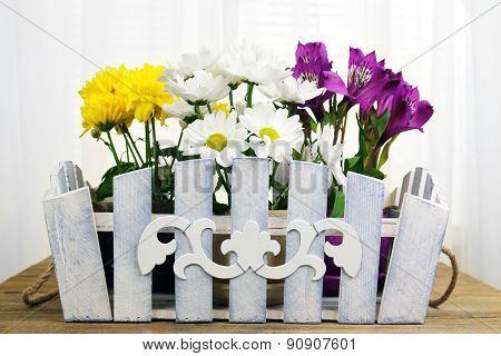 Beautiful flowers in ornamental flowerpot on fabric background