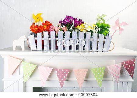 Beautiful flowers in ornamental flowerpot on mantelpiece