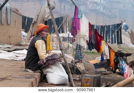 Indian Old Man Sits Near Clothesline On Ghat Near Sacred River Ganges In Varanasi