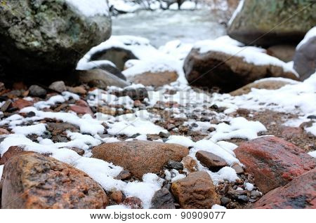 Stones in river covered with snow