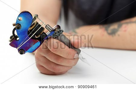 Hand of tattoo artist with tattoo machine at white table, closeup