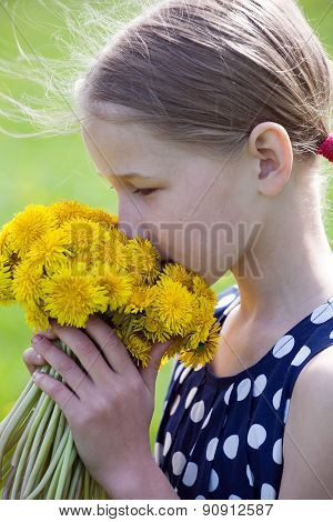 Young Girl Smelling A Bunch Of Dandelions