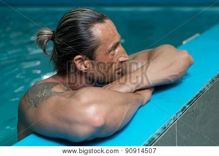 Mature Man Swimming In Pool At Resort