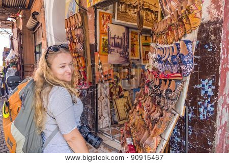 MARRAKESH, MOROCCO, APRIL 16, 2015: Female tourists watches hand made leather shoes displayed in medina