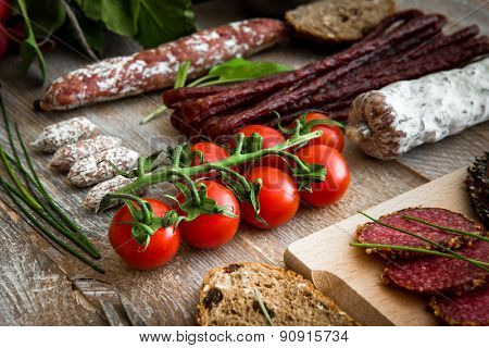 A bunch of cherry tomatoes with salami sausages, bread slices, greens on a wooden textured background