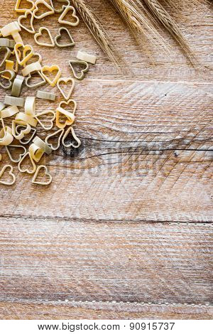 Heart shaped pasta with wheat ears on a wooden textured table