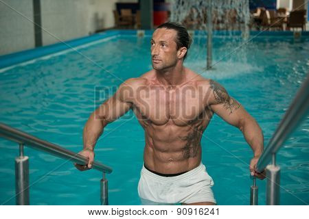 Man Resting Relaxed On Edge Of Swimming Pool