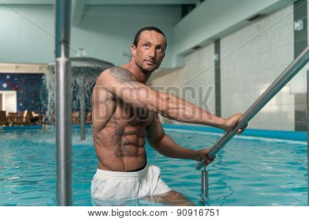 Man Resting His Arms At Edge Of Pool