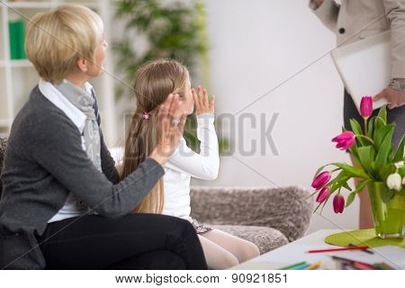 girl with  grandma sitting on sofa at home and  waving a greeting