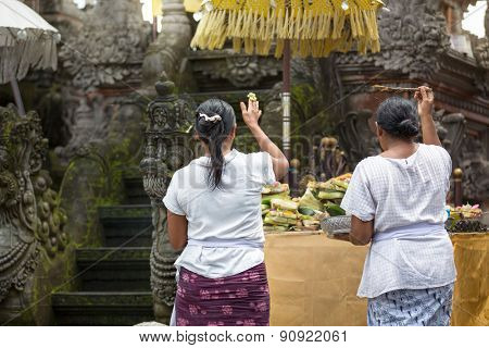 Two Asian woman praying in temple, Balinese ceremony