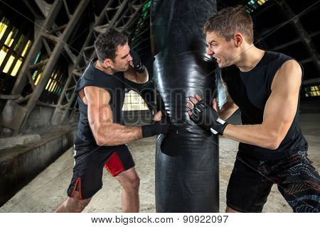 boxer man during boxing hitting heavy bag at training