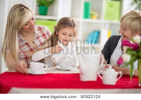 Cute girl serving tea her mom and grandma, mother and grandma looking at little girl who pours tea in cup