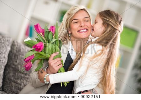 Little girl  giving flowers to his mom on mother's day