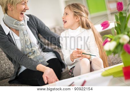 Grandmother and cute granddaughter laughing on sofa ta home